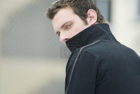 Man in sweatshirt looking over shoulder