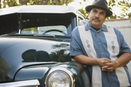 Middle-aged Hispanic man leaning against classic car