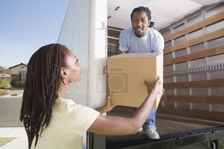 African man handing box to woman out of moving truck