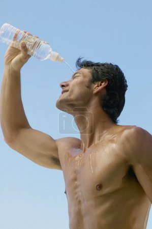 Bare-chested Asian man pouring water over head