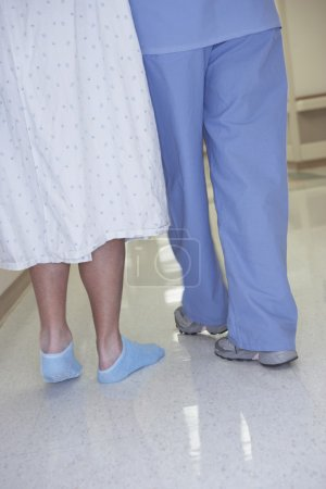 Rear view of nurse and patient walking in corridor