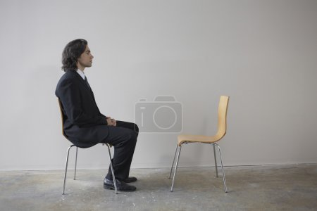 Businessman sitting across from empty chair