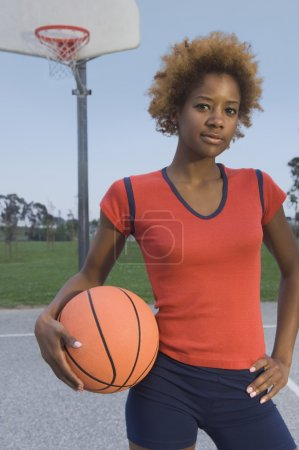 African woman holding basketball on court