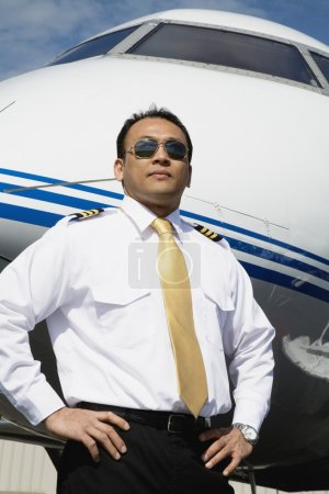 Asian male pilot standing near airplane
