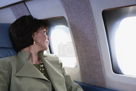 Businesswoman looking out widow on private airplane