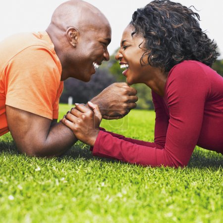 African couple laughing in grass