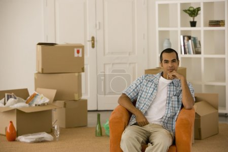 Young man sitting in new house