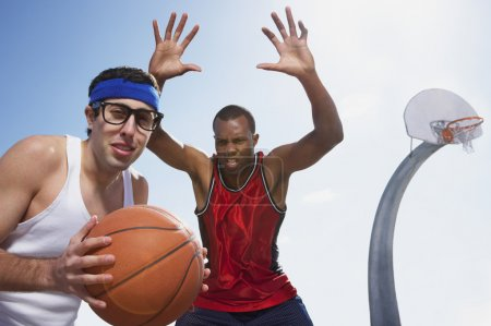 Nerdy man playing basketball with athlete