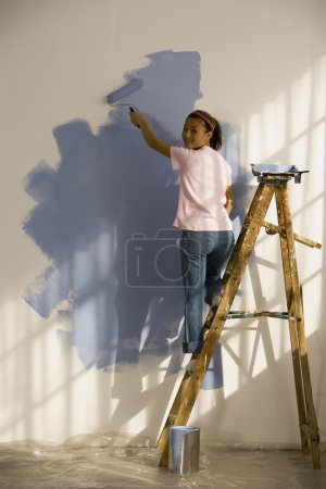 Asian woman painting interior of house