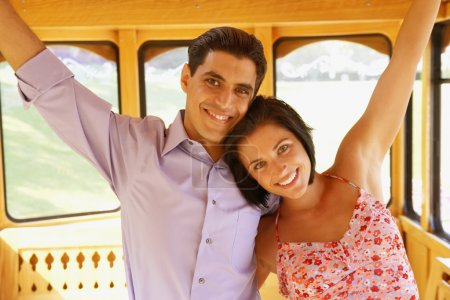 Young couple standing on trolley car