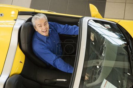 Hispanic car salesman sitting in new car