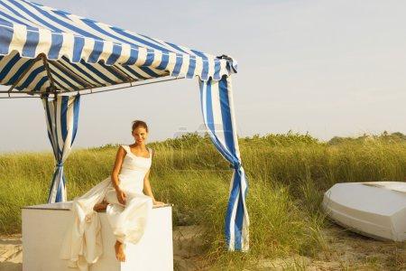Bride under tent at beach
