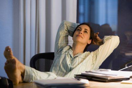 Hispanic businesswoman in pajamas at desk