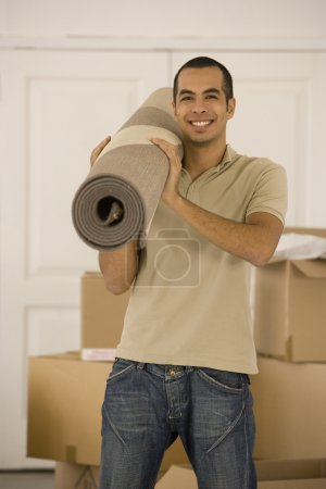 Man holding rolled rug in new house
