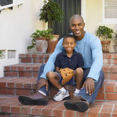 African American father and son sitting on porch steps