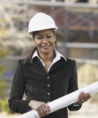 African American businesswoman holding blueprints