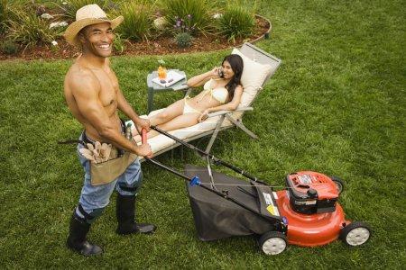 Man mowing lawn while woman sunbathes