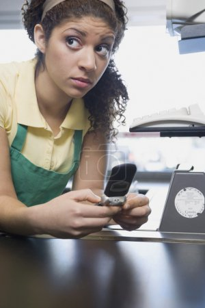 Mixed Race female grocery clerk dialing cell phone