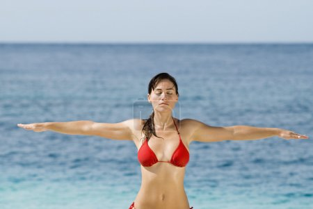 Hispanic woman practicing yoga at beach