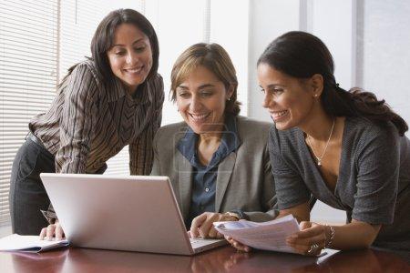 Hispanic businesswomen looking at laptop