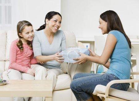 Hispanic girl giving gift to mother