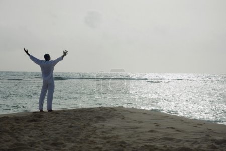 Hispanic man with arms raised at beach