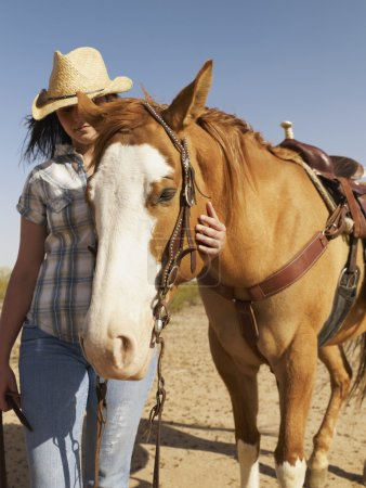 Hispanic woman standing next to horse