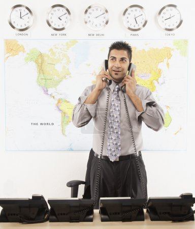 Indian businessman talking on two telephones