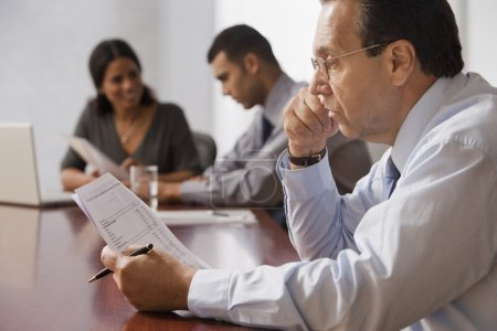 Hispanic businessman reading paperwork