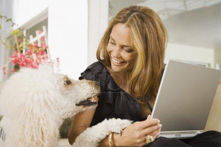 Hispanic woman smiling at dog