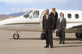 Multi-ethnic businesspeople in front of airplane