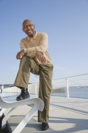 African American man with foot on bench