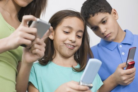 Multi-ethnic siblings looking at cell phones
