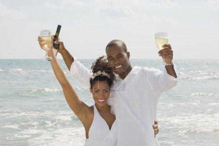 Multi-ethnic couple holding wine at beach