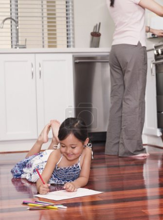 Mixed Race girl coloring on floor