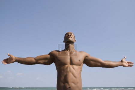 Bare-chested man with arms outstretched
