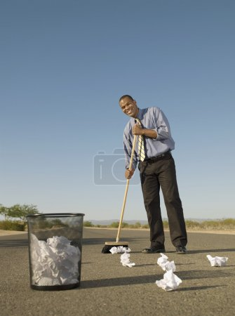 African businessman sweeping up paper in road