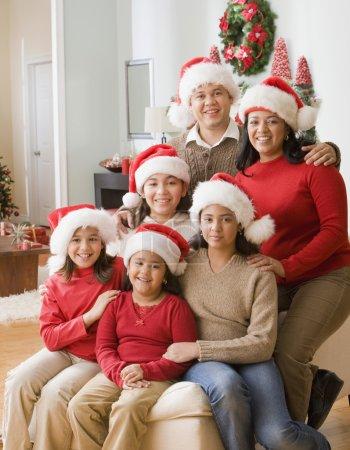 Hispanic family wearing Santa Claus hats