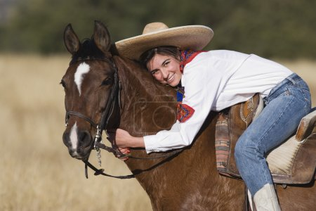 Hispanic woman hugging horse