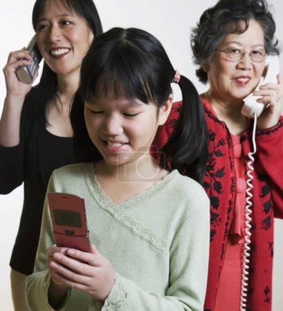 Multi-generational Asian family using telephone