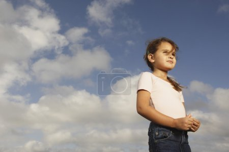 Mixed Race girl under blue sky
