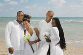 Multi-ethnic newlyweds hugging at beach