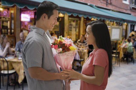Asian man giving flowers to girlfriend