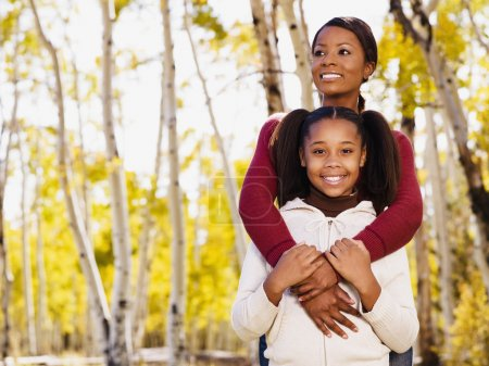 African mother hugging daughter in woods