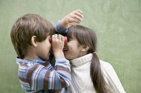 Hispanic siblings looking at each other through binoculars