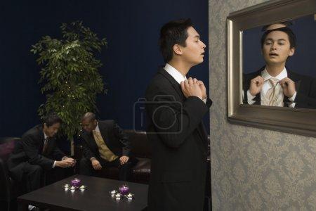 Mixed Race man adjusting necktie