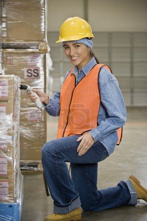 Hispanic warehouse worker scanning shipment