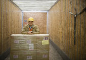 Asian warehouse worker with shipment in truck