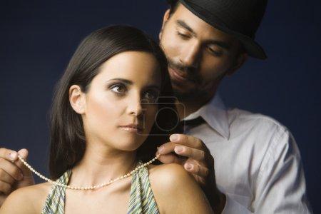 Hispanic man fastening wife's necklace