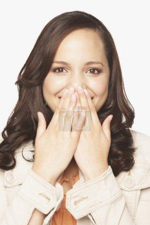 Hispanic woman covering mouth with hands